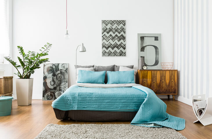 bedroom makeover with blue sheets and wall decorations